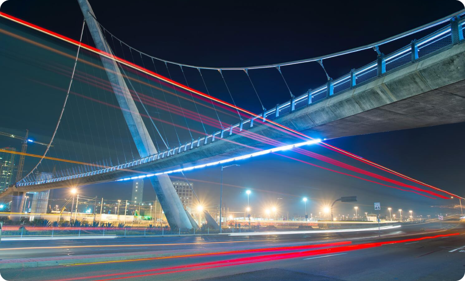 A flurry of vehicles pass beneath a bridge at lightning speed, representing how a hyperscale data center directs and manages high-volume data traffic.