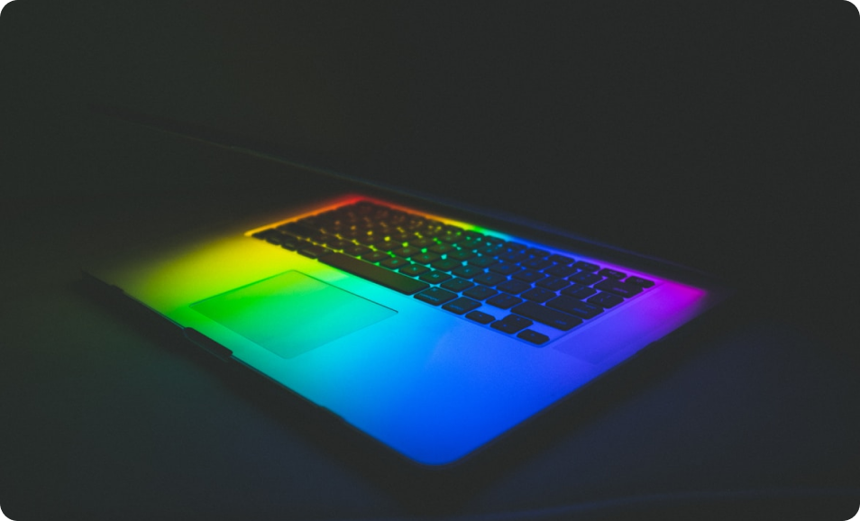 A laptop lit in rainbow light reflecting the colorful innovations being made in the networking world, including SD-WAN.