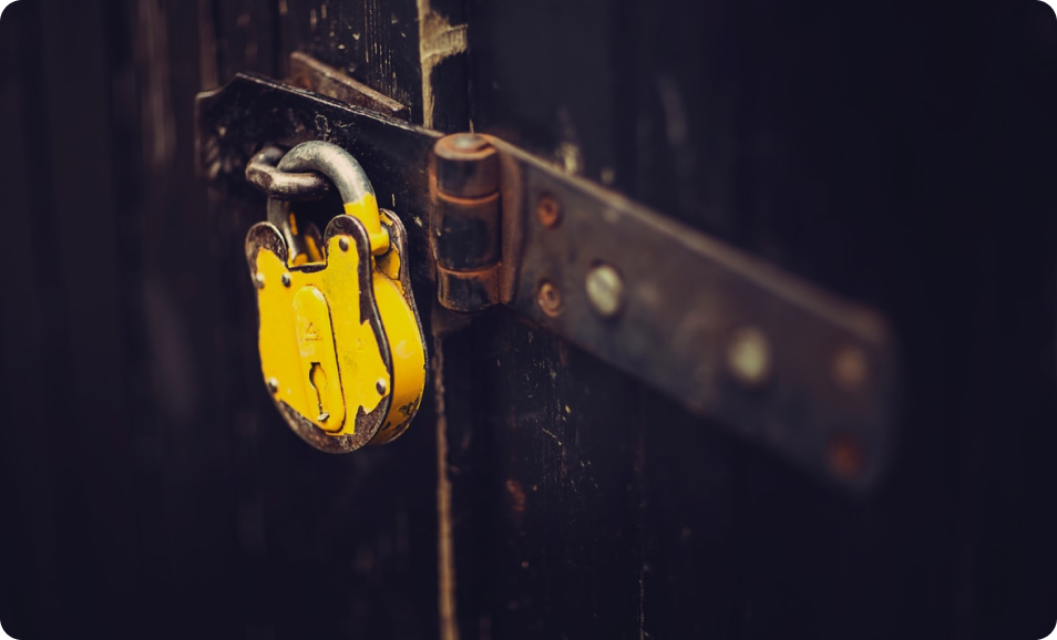 A heavy duty yellow padlock secures a thick metal door, representing the robust security measures necessary to protect data centers and network traffic.